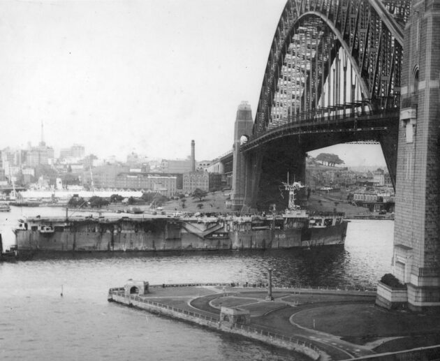 The Royal Navy aircraft carrier HMS Vindex passing under the Harbour Bridge with 300 ex Australian prisoners of war being returned home_Source City of Sydney